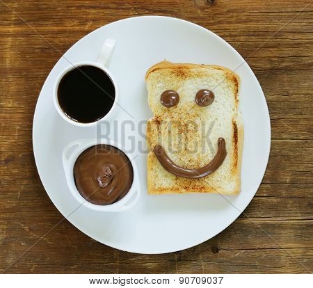 breakfast serving funny face on the plate (toast, chocolate spread and coffee)