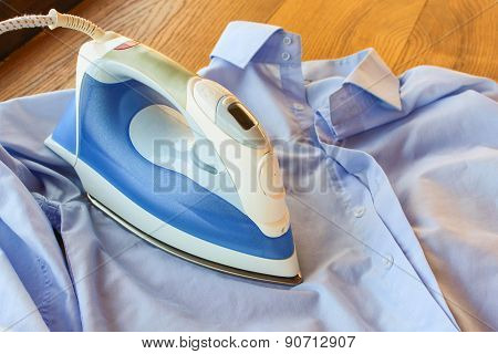 ironing shirt. Iron irons blue men's shirt.