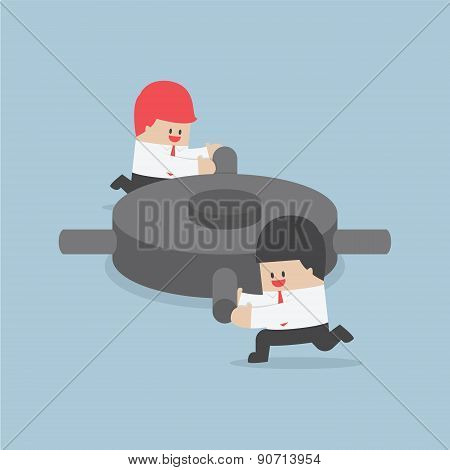 Businessman Helping Each Other To Push The Gear