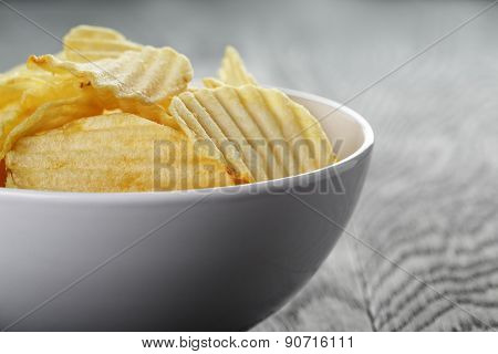 rippled organic chips in white bowl on wooden table