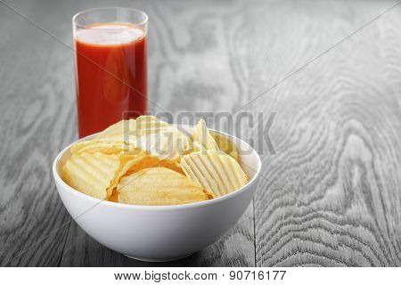 rippled organic chips in white bowl wit tomato juice on wooden table