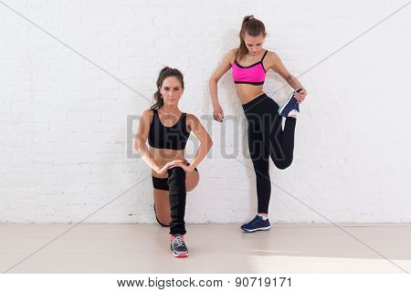 Group of fit women working stretching leg muscles warm up at gym fitness, sport, training and lifest