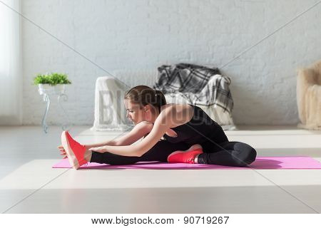 Fit woman high body flexibility stretching her leg to warm up doing aerobics gymnastics exercises at
