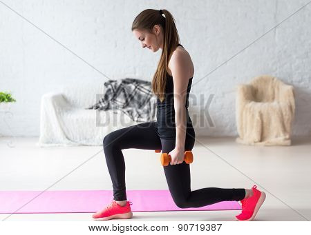 Athletic woman warming up doing weighted lunges with dumbbells workout exercise for butt legs at hom