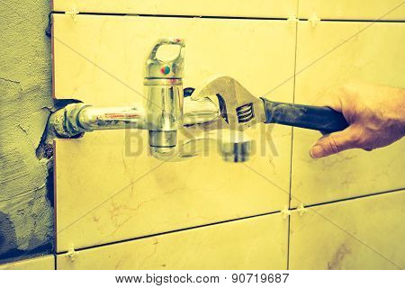 Vintage Photo Of Plumbers Hands Tightening A Water Pipe.