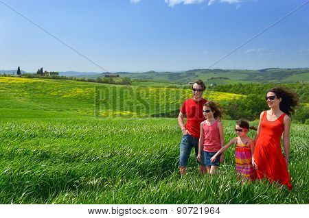 Happy family with children having fun outdoors on green field, spring vacation with kids in Tuscany