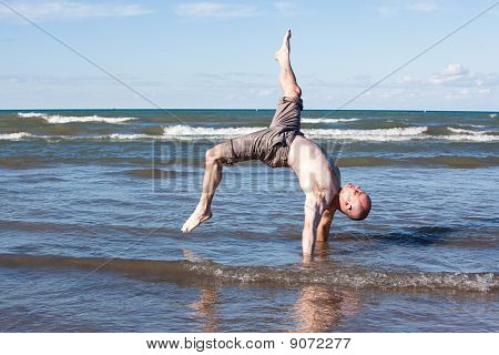 A man exercising at the beach