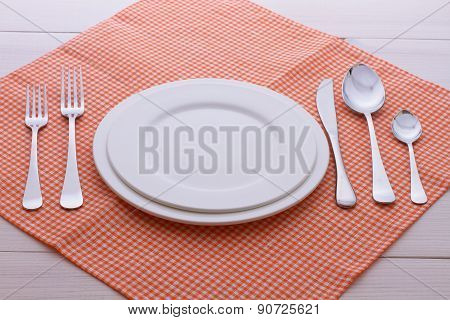 Empty plates, cutlery, tablecloth on white table for dinner.