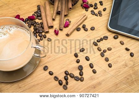 office worker's coffee break: composition of tablet wi-fi world composed of coffee beans cup of coff