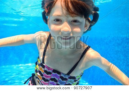 Happy girl swims in pool underwater, active kid swimming, playing and having fun