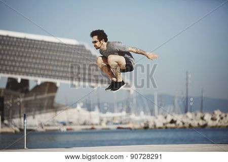 Young Tracer Athlete Jumping Over Building Roof Against Blue Sky Background, Free Runner Performing
