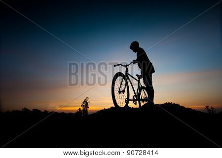 Silhouette Of Children And Bicycle At Sunset