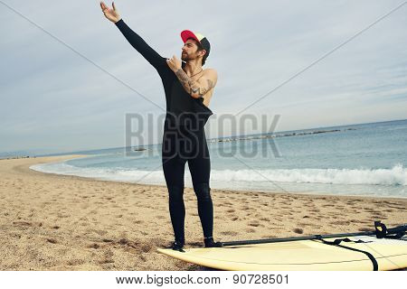 Portrait Of A Young Surfer Sports Man Wearing Surfing Neoprene Waterproof Suits And His Surfing
