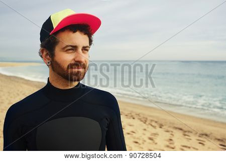 Portrait Of Handsome Young Surfer Man Standing At Sand Near Ocean