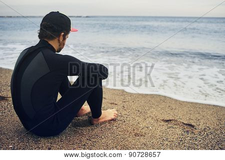 Portrait Of Handsome Young Surfer Man Sitting At Sand Near Ocean, Young Beautiful Surfer