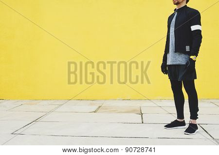 Sportsman In Black Wind Breaker Taking Break With Crossed Hands Standing On Yellow Wall Background.