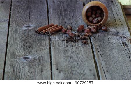 Wood Nut, Asterisks Of An Anise, A Stick Of Cinnamon And A Carnation On A Wooden Background