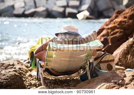 Old Woman Relaxing On The Beach.