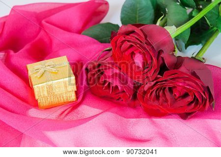 Golden Gift Box And Three Red Roses On A Pink Silk Scarf