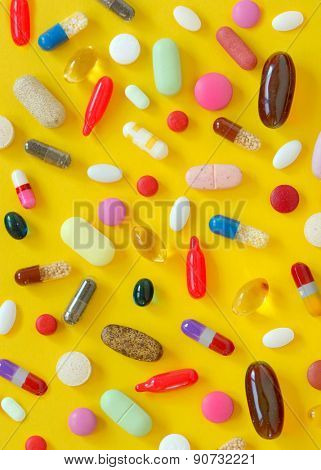 many different pills on yellow background