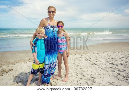 Cute family portrait on a beautiful beach. Horizontal photo of an attractive Mother and her two kids on beautiful beach day with the ocean in the background. Lots of copy space