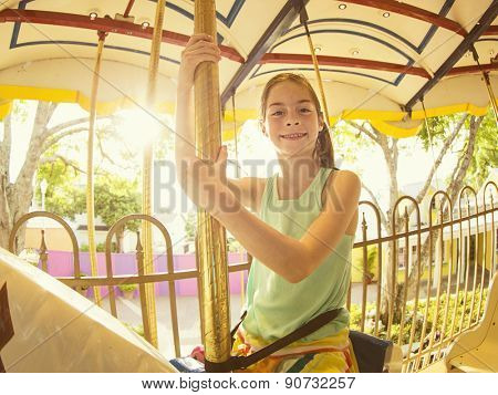 Cute smiling little girl riding on a Carnival Carousel at an amusement park or theme park. Warm afternoon sun in the background
