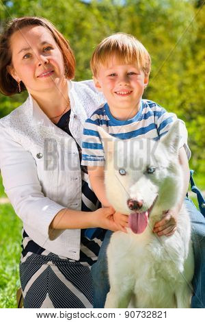 Mom with laughing son and dog sitting on grass in summer park