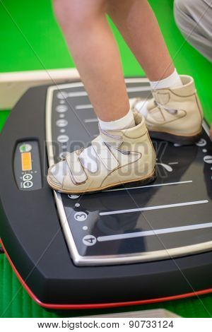 child feet on a vibrating training platform