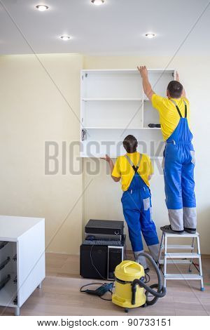 two male furniture adjusters in uniform hang wall drawer