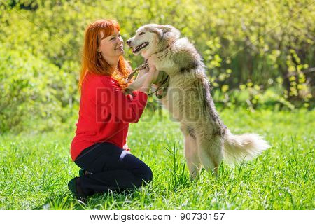 woman in red sweater and red hair smiling and playing with dog in park