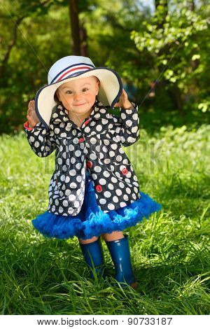 Little girl in hat jacket and boots laughing in park on background of green trees