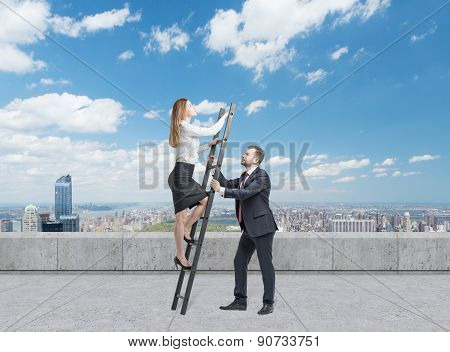 Businessman Is Holding A Ladder For The Business Lady. The Concept Of The Teamwork. On The Roof Terr