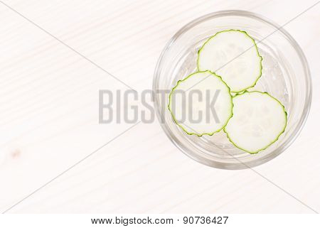 A Glass Of Water With Three Slices Of Fresh Cucumber On A Light Table, Top View
