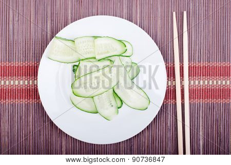 Japanese Cucumber Salad With Thinly Sliced Cucumbers In White Platejapanese Shelves, Lies On A Dark