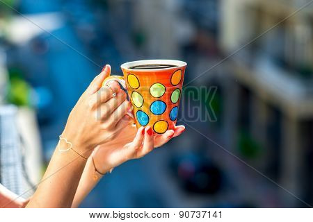 Holding colorful coffee cup on blured city background
