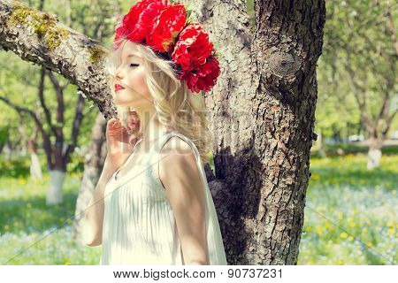 beautiful young gentle elegant young blond woman with red peony in a wreath of white blouse walking