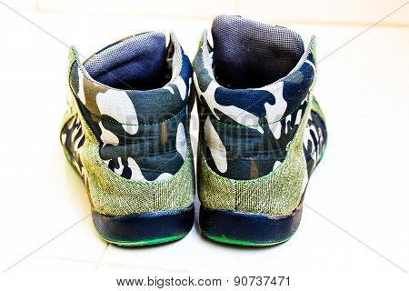 Military sneakers kept in broad sunlight on a plain background