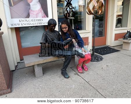 Girl and Sculpture of Boy Reading