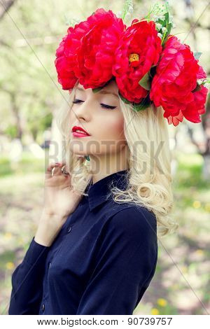 beautiful young gentle elegant young blond woman with a red crown of peony in a black blouse walks i