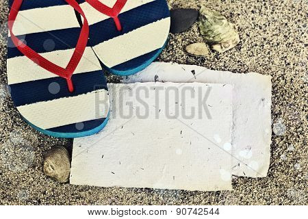 Beach background with copyspace, beach sand summer theme, straw hat and blue and white flip flops ov