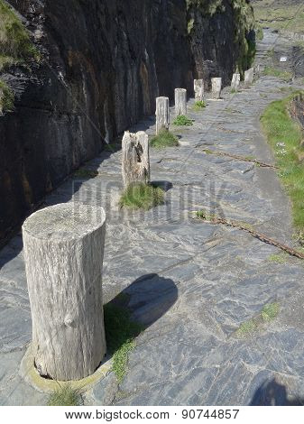 Cliff Lined Harbour Pathway With Mooring Logs