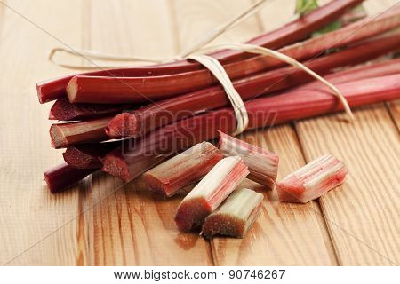 Bundle of rhubarb and chopped stalks on table, selective focus