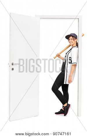 Full length portrait of a young female baseball player holding a baseball bat and leaning on the frame of an open door isolated on white background