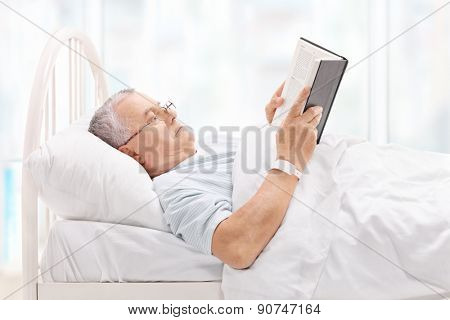 Mature patient lying in bed and reading a book in a hospital