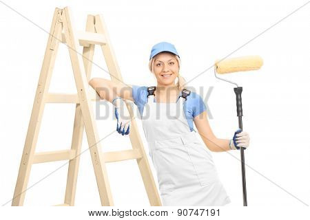 Young female painter holding a paint roller and leaning on a wooden ladder isolated on white background