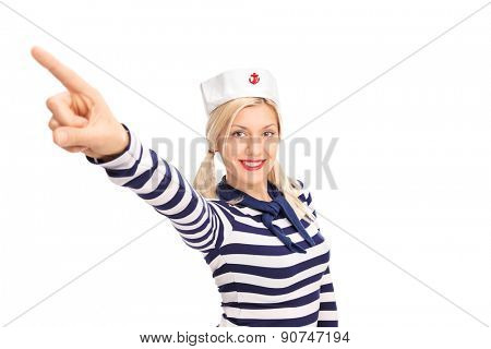 Beautiful female sailor with a sailor cap and a striped shirt pointing up with her finger and smiling isolated on white background