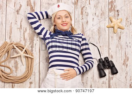 Carefree female sailor lying on a deck with binoculars and a rope beside her and looking at the camera