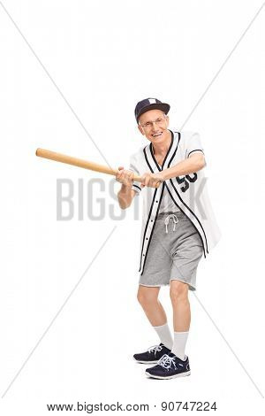 Full length portrait of a senior in a baseball jersey swinging a baseball bat and looking at the camera isolated on white background
