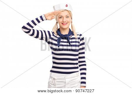 Young blond woman in a sailor outfit saluting towards the camera and smiling isolated on white background