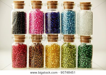 Tiny glass bottles filled with a different colors of beads